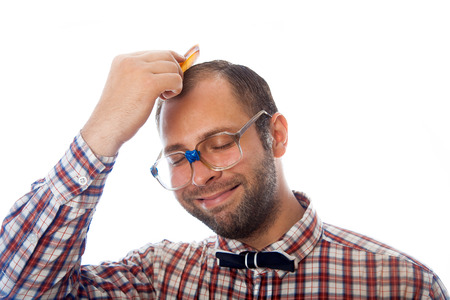classbook: unshaven man nerd combing hair in studio on white background