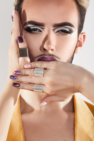 gay men: Close up retrato de modelo de la moda gay con la barba y el maquillaje. Estudio de disparo. Vertical. Foto de archivo