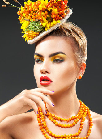 rowanberry: Lovely young fashion model with bouquet of rowan on head and rowanberry on neck looking away