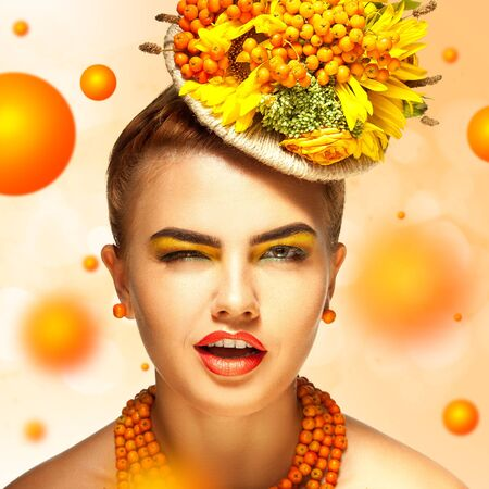 blink: young fashion girl with beautiful makeup blink on orange background Stock Photo