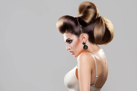 woman hairstyle: Profile portrait of young sexy woman with creative hairstyle and nice makeup in studio