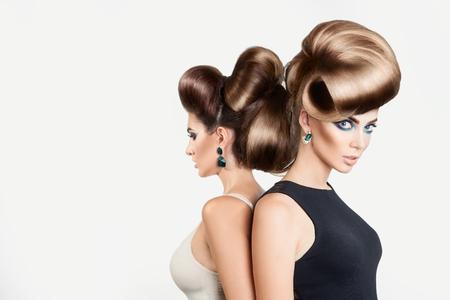 スタジオで二人の美しい女性。創造的な髪型と灰色の背景に素敵なメイクの両方