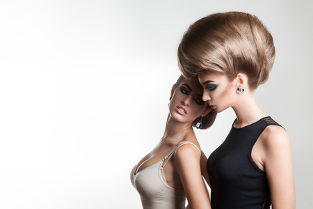 hairstyle: young beautiful ladies in studio with creative hairstyle on gray background