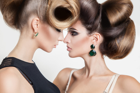 Portret van twee sexy vrouwen in studio met volume creatief kapsel te kijken naar elkaar in de studio