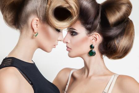 lesbianas: Retrato de dos mujeres atractivas en estudio con el peinado creativo volumen mirando a los demás en el estudio Foto de archivo