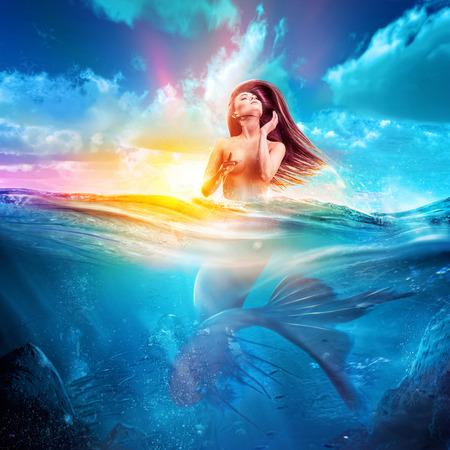nue plage: sirène sexy émerge de la mer au coucher du soleil. art conept