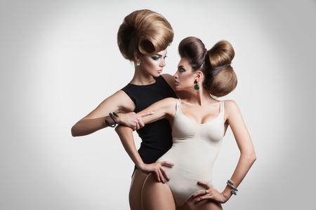 maquillage: Belles filles de la mode avec coiffure cr�ative regarder les autres eash en studio sur fond gris