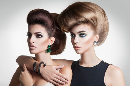 hairstyles: Closeup portrait of two beauty fashion women with creative volume hairstyle and nice makeup in studio