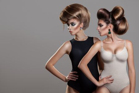hairstyles: Horizontal portrait of two sexy women with creative hairstyle and nice makeup in studio