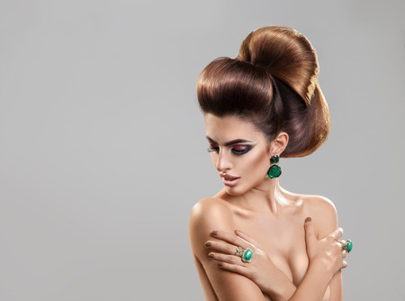 hairstyles: Horizontal portrait of young fashion model with creative hairstyle and nice makeup in studio Stock Photo