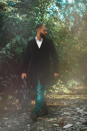 elegant business man: Giovane elegante uomo d'affari guarda lontano piedi attraverso il parco all'aperto
