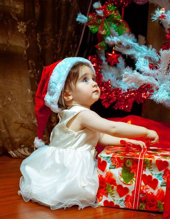 first: Cute little baby girl in Santa hat opens her first Christmas present.