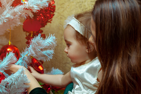 decorates: Mother decorates the Christmas tree with her little baby girl.