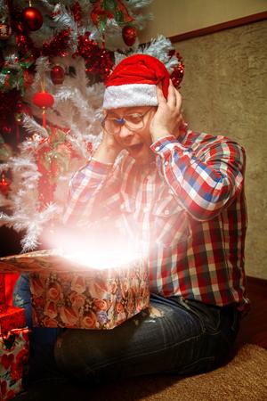 nerd: Surprised nerd opens a gift. Stock Photo