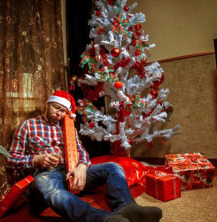 borracho: empollón borracho en el sombrero de santa que miente bajo el árbol de Christma con un montón de regalos. Foto de archivo