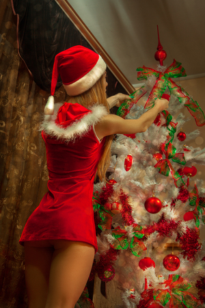 sexy girl dressed as Santa Claus decorates the Christmas tree.