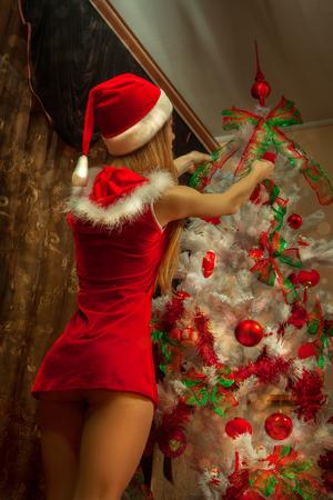 decorates: sexy girl dressed as Santa Claus decorates the Christmas tree.