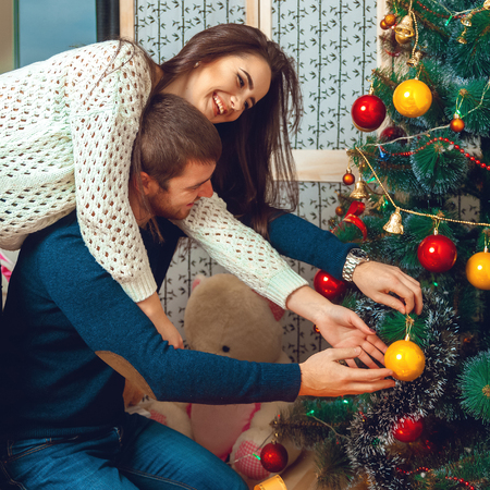 decorates: Lovely couple decorates Christmas tree. New year.