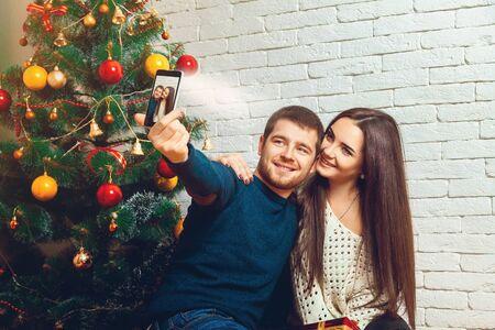 hacer el amor: amantes de la pareja joven que hace selfie Navidad. Año nuevo. Humor navideño.