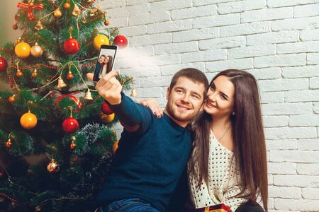 make love: loving young couple making Christmas selfie. New Year. Christmas mood.