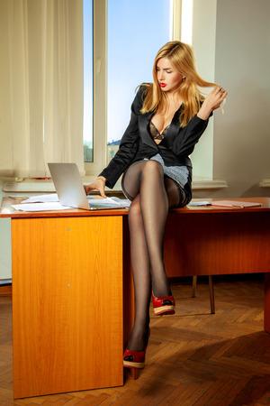 busty: Foto de gerente de oficina tetona sentado en la mesa y trabajar en la computadora portátil. Concepto de negocio Foto de archivo
