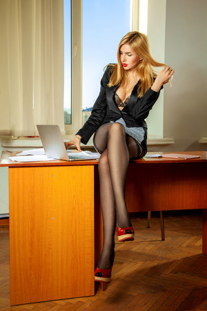 Photo of busty office manager sitting on table and working on laptop. Business concept Stock Photo