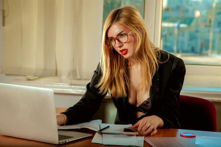性的な金髪白人秘書のオフィスにラップトップ コンピューターでの作業します。ビジネス コンセプト