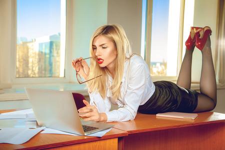 oficinista: secretaria de la oficina rubia sexual en camisa que presenta en la tabla. Concepto de negocio
