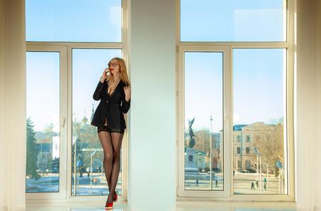 Slim sexual blonde secretary standing on windowsill. Business concept