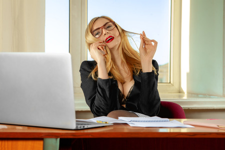 busty: Fashionable busty secretary talking phone in office. Business concept Stock Photo