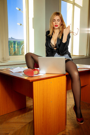 Gorgeous lustful secretary with laptop between the legs. Business concept Stock Photo