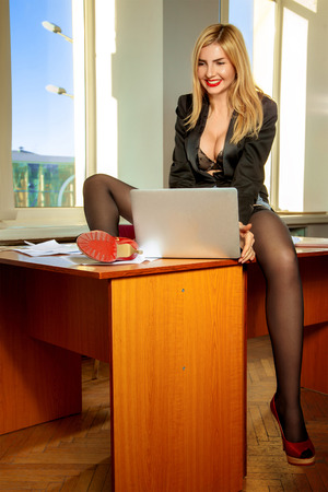 lustful: lustful secretary sits on a table with a laptop between his legs. Business concept
