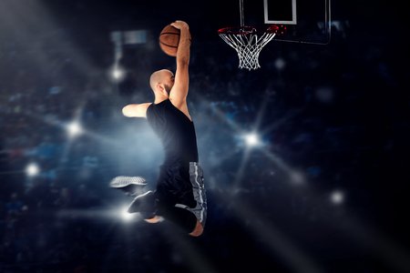 dunk: Basketball player jumping to the ring and makes slam dunk. NBA game. Basketball game. Sportsman plays basketball. Stock Photo