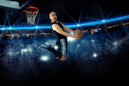 Horizontal photo of basketball player in the game makes reverse slam dunk. NBA. Basketball game. Sportsman plays basketball.