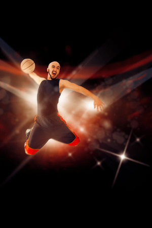 dunk: Bald baksetball player in the game makes slam dunk with one hand. Sportsman plays basketball. NBA game. Basketball game. Stock Photo
