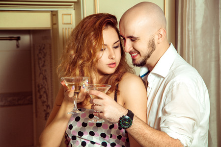 home party: Flirting couple with martini at home party. Celebrate, disco, party, nightlife, entertainment, friendship concept. Stock Photo