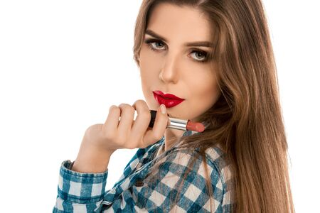make up artist: Close up photo of young caucasian girl with lipstick in hand isolated on white background in studio. Makeup artist. Creative make up artist. Stock Photo