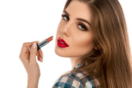 make up artist: Close up portrait of young beautiful girl with lipstick in hand isolated on white background in studio. Makeup artist. Creative make up artist.