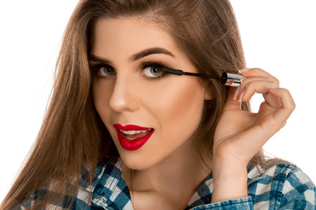 make up artist: closeup portrait of a girl with a make-up brush for lash in hands isolated on white background in studio. Makeu partist. Creative make up artist. Stock Photo