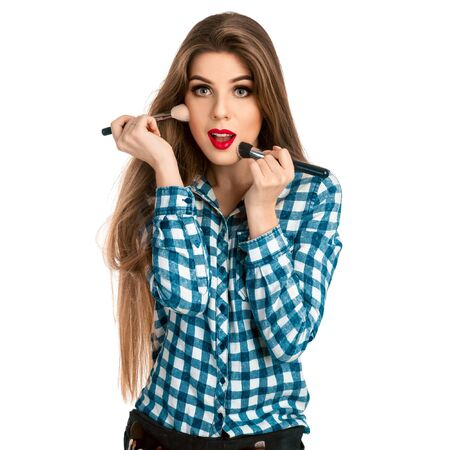 make up artist: Fun young girl in casual clothes makes a make-up isolated on white background in studio. Makeup artist. Creative make up artist.