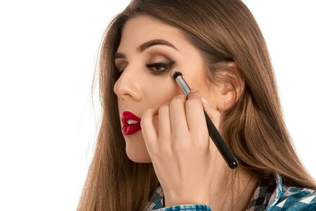 make up artist: girl makes a make-up with brush in studio on white background isolated. Makeup artist. Creative make up artist.