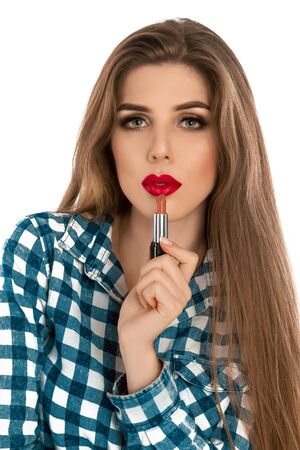 make up artist: Vertical photo of young beautiful stylish girl with lipstick in hand isolated on white background in studio. Makeup artist. Creative make up artist. Stock Photo