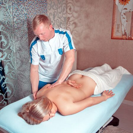 excitation: Adult woman in spa salon having body relaxing massage. Beautiful blonde relaxing in spa. health, beauty, resort and relaxation concept
