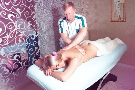 beauty resort: Man masseur doing massage for a young sweet blonde woman in spa salon. health, beauty, resort and relaxation concept. Beautiful blonde relaxing in spa. Stock Photo