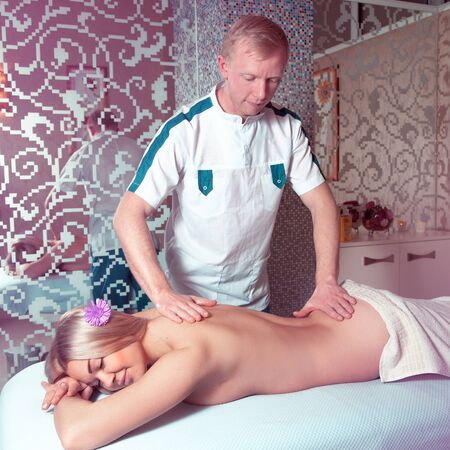 beauty resort: Photo of masseur doing massage a young beautiful blonde woman in a spa salon. health, beauty, resort and relaxation concept. beautiful blonde relaxing in spa.