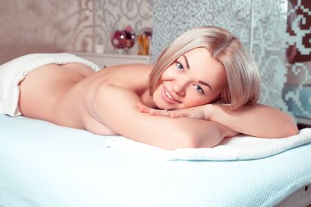 beauty resort: smiling young blonde girl relaxing in spa massage salon. health, beauty, resort and relaxation concept. Beautiful blonde relaxing in spa.