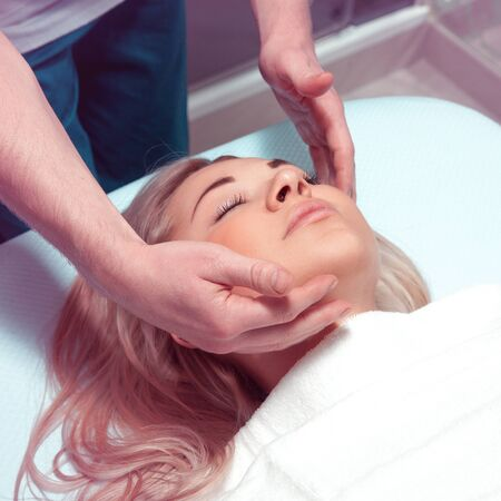 beauty resort: Square photo of Beautiful young woman receiving facial massage with closed eyes in a spa salon. health, beauty, resort and relaxation concept. Beautiful blonde relaxing in spa.