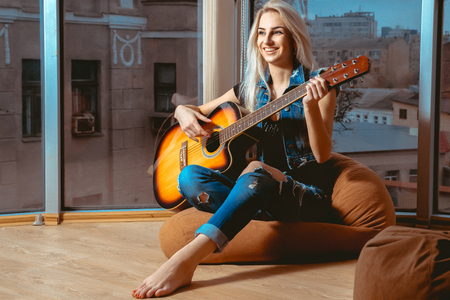 nude girl sitting: lovely girl smiling and having fun playing the guitar. Girl with guitar. Woman playing guitar. leisure with guitar.