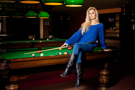 pool cue: Adorable blonde fashion woman posing on pool table with the cue. Stock Photo