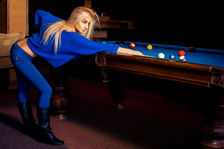 sexual: Adorable young beautiful blonde concentrated on pool billiard game. Stock Photo